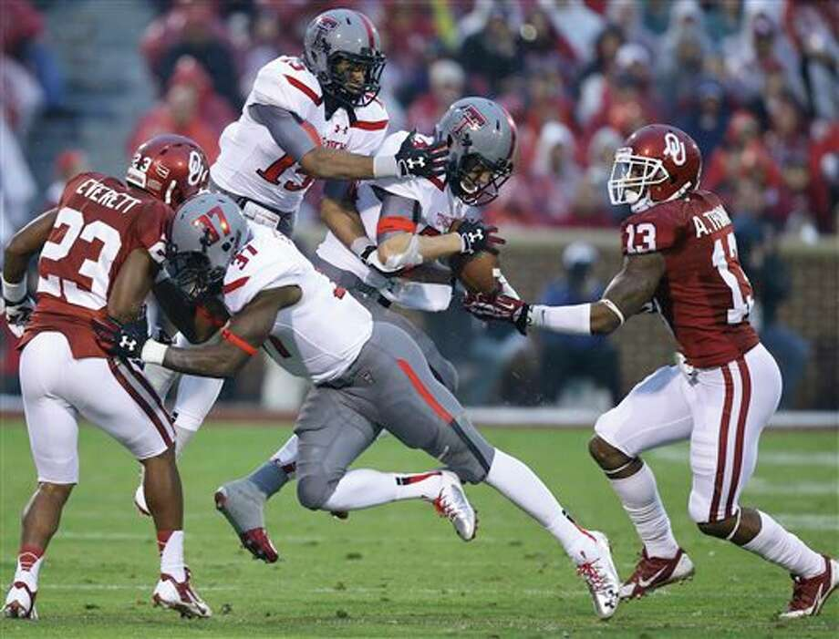 (File Photo) Texas Tech Summitt Hogue, center, grabs an onside kick between teammate Keenon Ward (15) and Oklahoma defensive back Amad Thomas (13) in the third quarter of an NCAA college football game in Norman, Okla., Saturday, Oct. 26, 2013. Oklahoma won 38-30. Texas Tech linebacker Bobby Esiaba and Oklahoma defensive back Kass Everett (23) are in on the play. (AP Photo/Sue Ogrocki) Photo: Sue Ogrocki / AP