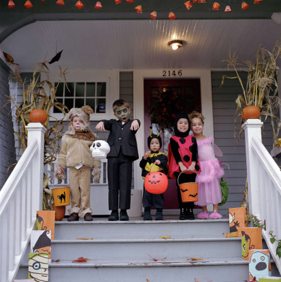 Five children standing on porch, wearing Halloween costumes, portrait Photo: Ryan McVay / (c) Ryan McVay