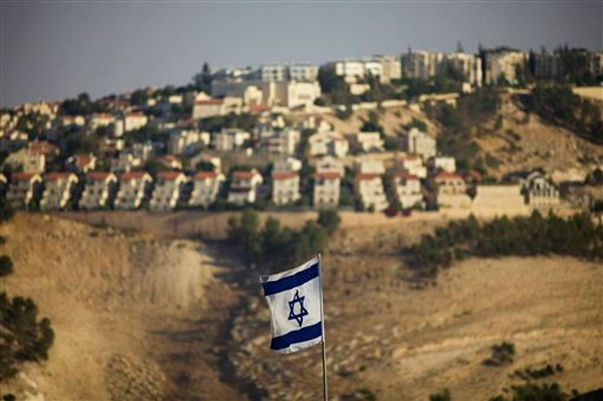 FILE - In this Monday, Sept. 7, 2009 file photo, an Israeli flag is seen in front of the West Bank Jewish settlement of Maaleh Adumim on the outskirts of Jerusalem. Israel on Wednesday, Oct. 30, 2013, announced plans to build 1,500 new homes in east Jerusalem, the part of the city claimed by the Palestinians, just hours after it freed a group of Palestinian prisoners as part of a deal to set peace talks in motion. (AP Photo/Bernat Armangue, File)