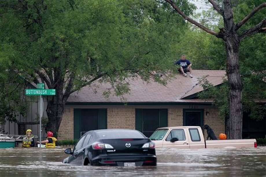 A man sits on top of a home on Buttonbush Drive in southeast Austin, Texas, on Thursday, Oct. 31, 201 Heavy overnight rains brought flooding to the area. The National Weather Service said more than a foot of rain fell in Central Texas, including up to 14 inches in Wimberley, since rainstorms began Wednesday. (AP Photo/The Austin American-Statesman, Deborah Cannon) AUSTIN CHRONICLE OUT, COMMUNITY IMPACT OUT, INTERNET MUST CREDIT PHOTOGRAPHER AND STATESMAN.COM, NO SALES Photo: Deborah Cannon / American-Statesman