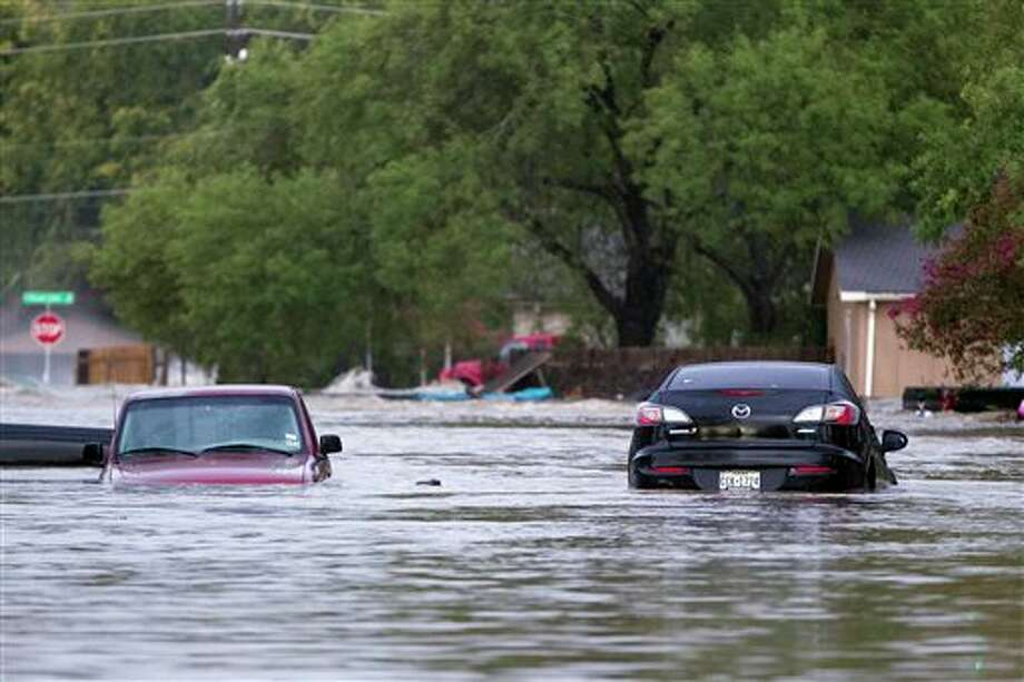 Cars are partially submerged on Quicksilver Blvd in southeast Austin, Texas, on Thursday, Oct. 31, 2013. Heavy overnight rains brought flooding to the area. The National Weather Service said more than a foot of rain fell in Central Texas, including up to 14 inches in Wimberley, since rainstorms began Wednesday. (AP Photo/The Austin American-Statesman, Deborah Cannon) AUSTIN CHRONICLE OUT, COMMUNITY IMPACT OUT, INTERNET MUST CREDIT PHOTOGRAPHER AND STATESMAN.COM, NO SALES Photo: Deborah Cannon / American-Statesman