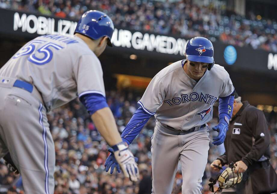 Troy Tulowitzki low-fives Blue Jays teammate Russell Martin after hitting a second-inning solo homer against Matt Cain. Photo: Eric Risberg, Associated Press