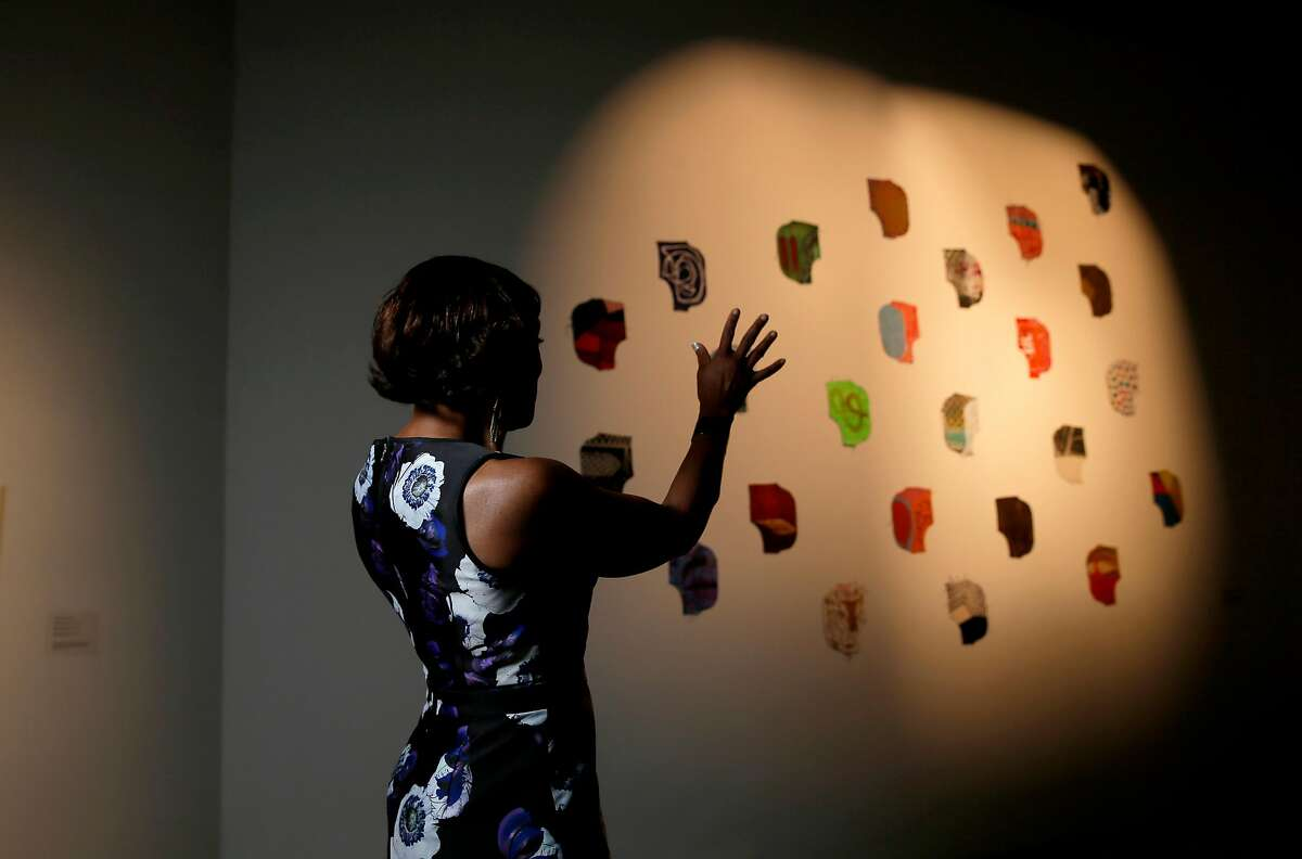 """Maria Jenson on Tues. May 10, 2016, is the new director of SOMART. Jenson is near a work by Marcius Noceda, """"Head Hunters of Hunter Point"""", 2015, part of a show curated by the Pacific Islanders Cultural Center in San Francisco, California."""