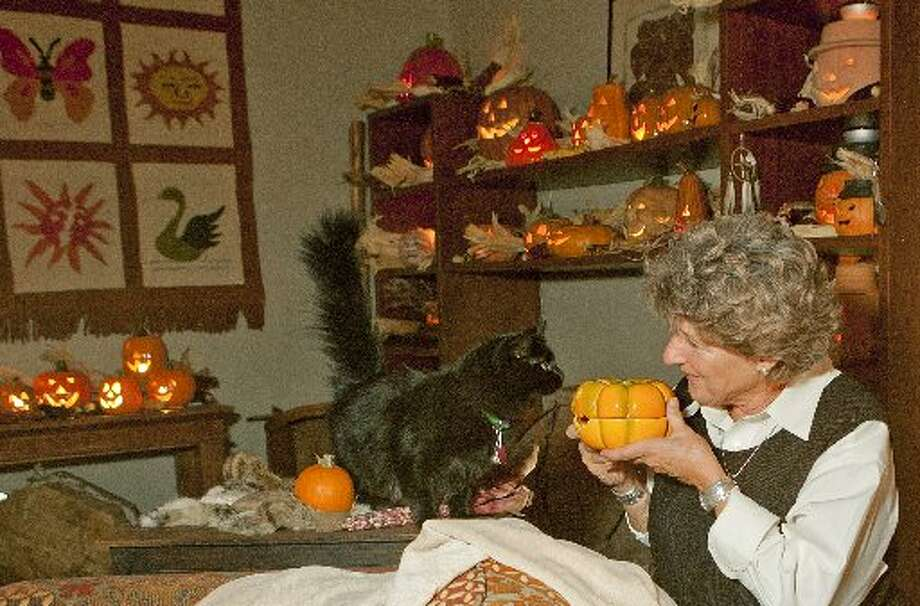 Brenda Rathjen and her 2-year-old rescue cat Loonie check out one of the 150 jack-o-lanterns in Rathjen's house on Wednesday. Photo: James Durbin/Reporter-Telegram
