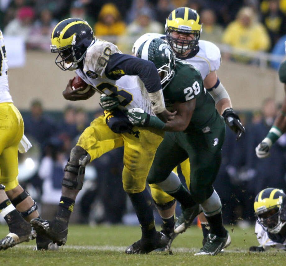 Michigan quarterback Devin Gardner, left, is sacked by Michigan State's Denicos Allen (28) during the third quarter of an NCAA college football game, Saturday, Nov. 2, 2013, in East Lansing, Mich. Michigan State won 29-6. (AP Photo/Al Goldis) Photo: Al Goldis
