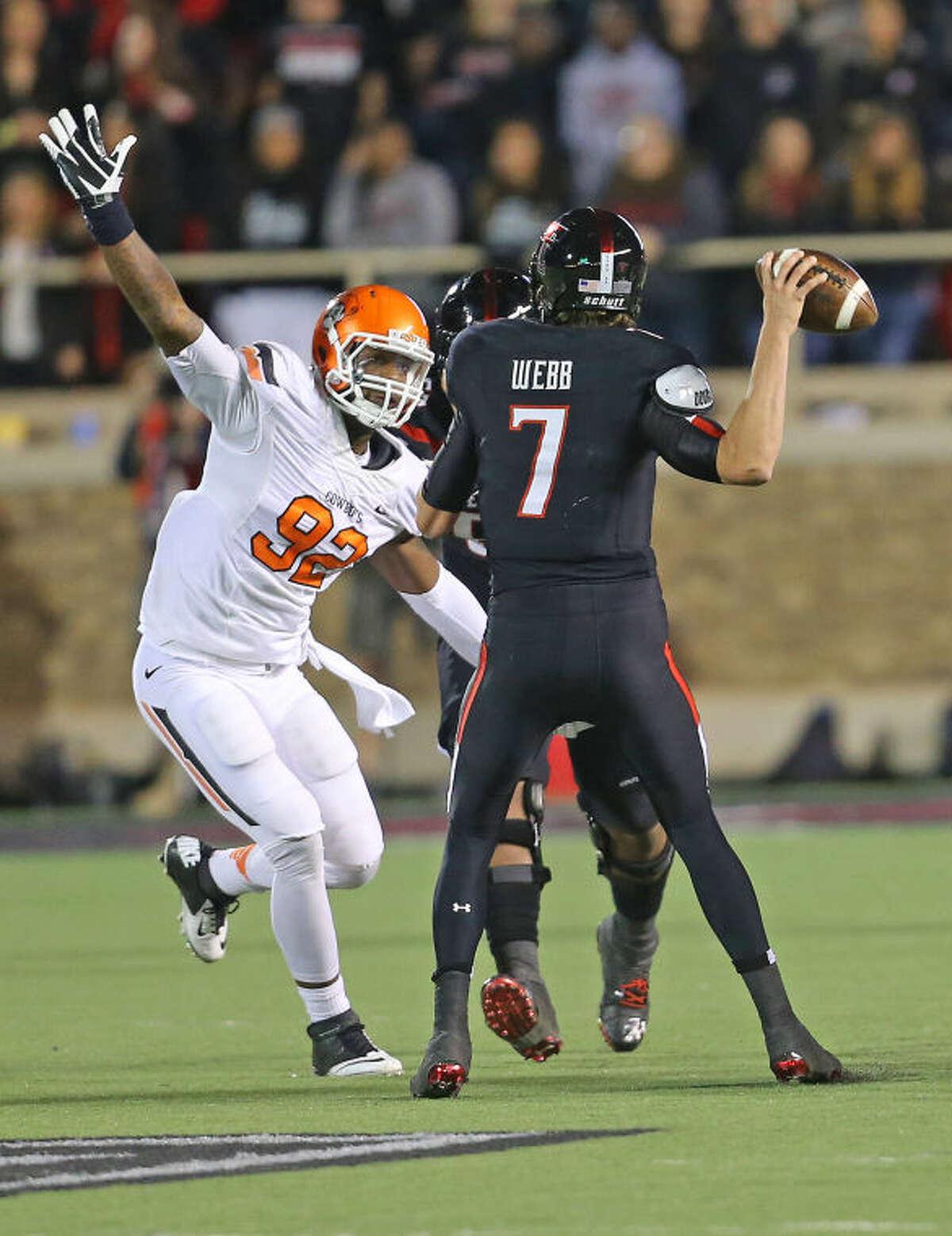 Oklahoma State defender Jimmy Bean puts presssure on Texas Tech quarterback Davis Webb (7) in Saturday Night's Bug XII game in Lubbock at the Jones A T & T Stadium.