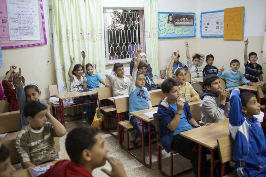 Young Syrian refugees pictured in a classroom at the Latin School Ader-Karak, in Karak, Jordan. The school serves 120 Syrian refugees and teaches core subjects such as Math, Science, English, Arabic, as well as physical education, arts and crafts, and trauma counseling. Catholic Relief Services is supporting Caritas Jordan to help more than 140,000 Syrian refugees across the country. This help includes essential living items, food, medical assistance, hygiene, education for children and trauma counseling. Photo: Andrew McConnell