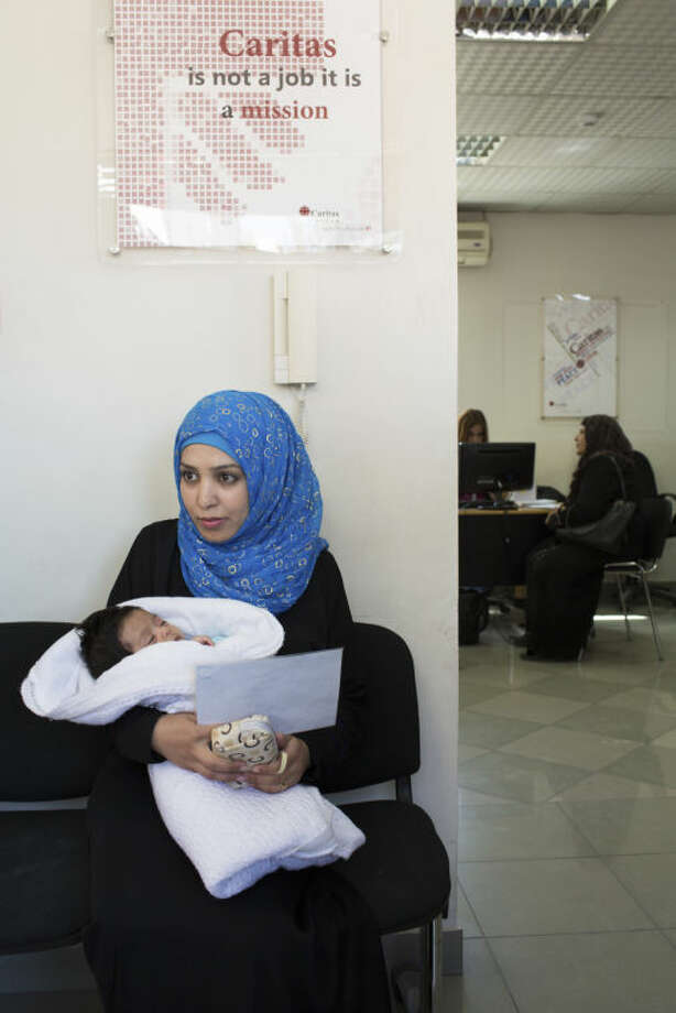 Syrian reufgee Raba'a, 19, from Deraa, with her 1 month old baby Tamer, at the Caritas clinic in Amman, Jordan. Raba'a does not have her marriage certificate so is unable to get a birth certificate for her son, and without a birth certificate she is unable to get the necessary care for her son: vaccinations, health care, support of any kind. She is receiving critical medical support at Caritas during this time. On this day she was also receiving advice on how to obtain a birth certificate, as well as vouchers for diapers and milk. She is living with her mother and siblings in a two-room apartment, her husband is in Syria. Catholic Relief Services is supporting Caritas Jordan to help more than 140,000 Syrian refugees across the country. This help includes essential living items, food, medical assistance, hygiene, education for children and trauma counseling. Photo: Andrew McConnell