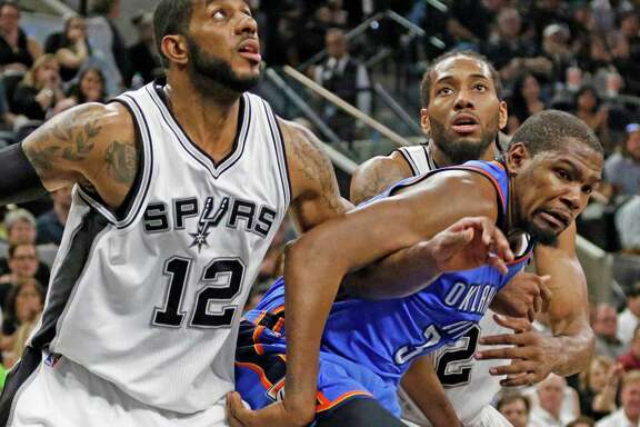 SAN ANTONIO,TX - MAY 10:  LaMarcus Aldridge  #12 and Kawhi Leonard #2 of the San Antonio Spurs try to outmuscle Kevin Durant #35 of the Oklahoma City Thunder for a rebound in game Five of the Western Conference Semifinals during the 2016 NBA Playoffs at AT&T Center on May 10, 2016 in San Antonio, Texas.  NOTE TO USER: User expressly acknowledges and agrees that , by downloading and or using this photograph, User is consenting to the terms and conditions of the Getty Images License Agreement.