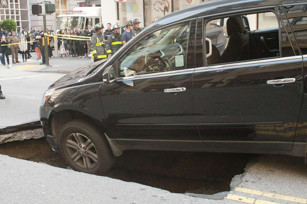 After the occupants were evacuated from the vehicle, SFPD taped off the block of Mission Street between Second and New Montgomery streets at approx. 6:15pm . Firefighters wait for the tow truck to arrive to pull the vehicle from the sinkhole. The accident occurred at approximately 5:50 p.m. on May 10, 2016. Franchon Smith/Special to The Chronicle.