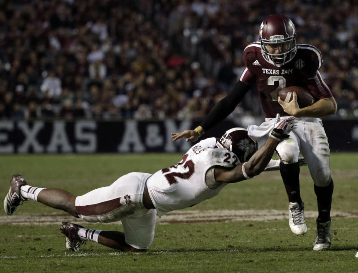 Texas A&M quarterback Johnny Manziel (2) rushes as Mississippi State linebacker Matthew Wells (22) reaches to tackle him during the fourth quarter of an NCAA college football game Saturday, Nov. 9, 2013, in College Station, Texas. Texas A&M won 51-41. (AP Photo/David J. Phillip)