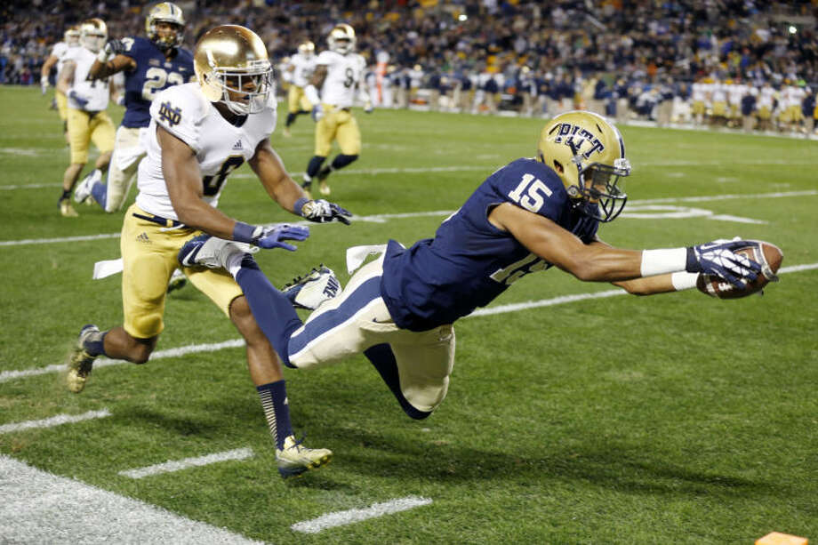 Pittsburgh wide receiver Devin Street (15) dives into the end zone past Notre Dame cornerback KeiVarae Russell (6) for a touchdown in the third quarter of an NCAA college football game on Saturday, Nov. 9, 2013, in Pittsburgh. Pittsburgh won 28-21.(AP Photo/Keith Srakocic) Photo: Keith Srakocic