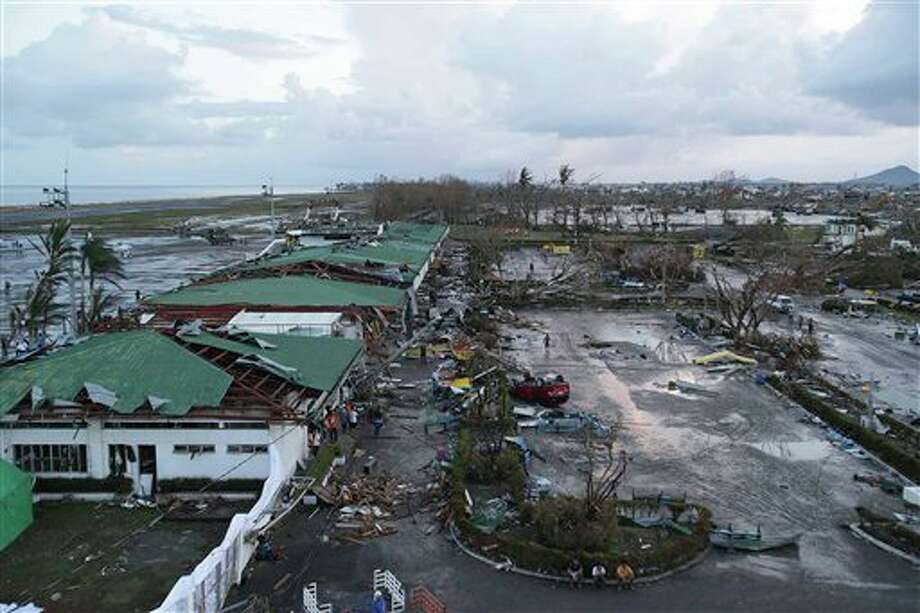 "The airport devastated by powerful Typhoon Haiyan that slammed into Tacloban city, Leyte province, Philippines is seen on Saturday, Nov. 9, 2013. The central Philippine city of Tacloban was in ruins Saturday, a day after being ravaged by one of the strongest typhoons on record, as horrified residents spoke of storm surges as high as trees and authorities said they were expecting a ""very high number of fatalities."" (AP Photo/Aaron Favila) Photo: Aaron Favila / AP2013"