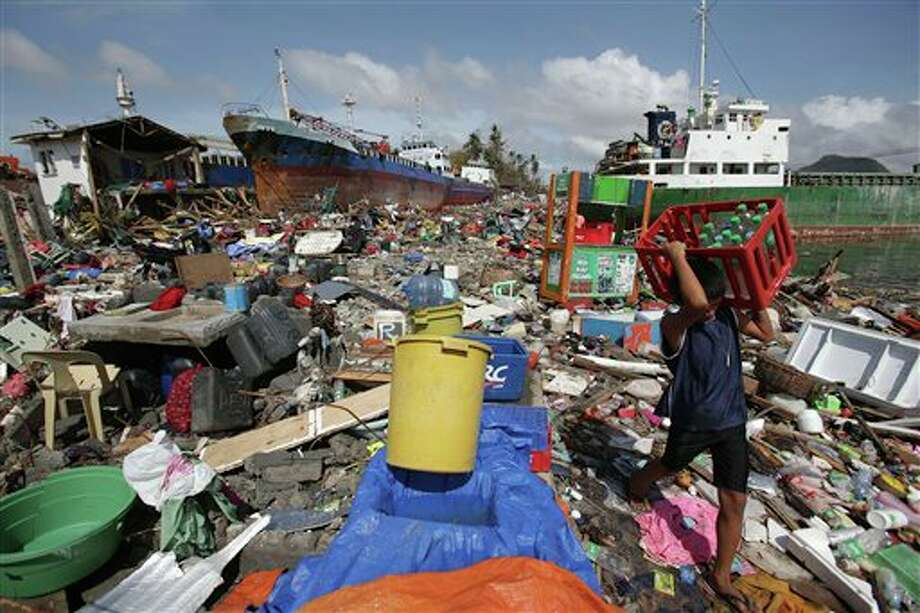 A Filipino boy carries bottled water amongst the damaged houses where a ship was washed ashore in Tacloban city, Leyte province, central Philippines on Sunday, Nov. 10, 2013. The city remains littered with debris from damaged homes as many complain of shortages of food and water and no electricity since Typhoon Haiyan slammed into their province. Haiyan, one of the most powerful storms on record, slammed into six central Philippine islands on Friday, leaving a wide swath of destruction and scores of people dead. (AP Photo/Aaron Favila) Photo: Aaron Favila / AP