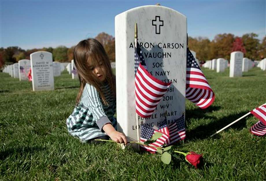 Sydney Kelly, 3, places a rose on the grave of Elite Navy SEAL member Aaron Carson Vaughn in Section 60 of Arlington National Cemetery in Arlington, Va., Monday, Nov. 11, 2013. on Veterans Day. Aaron Carson Vaughn died Aug. 6, 2011, in Wardak province, Afghanistan, of wounds suffered when the CH-47 Chinook helicopter in which he was riding was shot down. Sydney's mother Ginny Kelly is a family friend. (AP Photo/Carolyn Kaster) Photo: Carolyn Kaster / AP