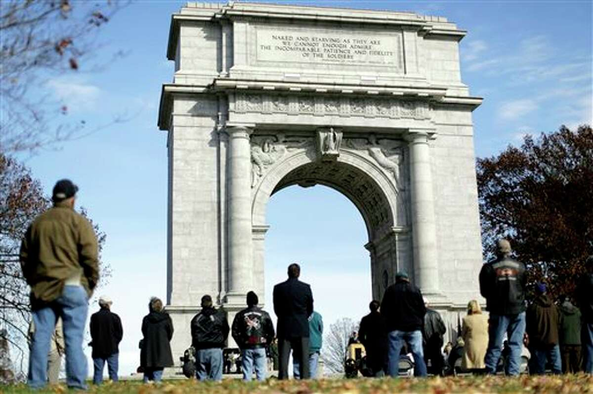 People gather for a Veterans Day commemoration ceremony at the National Memorial Arch, Monday, Nov. 11, 2013, at the Valley Forge National Historical Park in Valley Forge, Pa. Across the nation, Americans are commemorating the service and sacrifice of military service members this Veterans Day. (AP Photo/Matt Rourke)