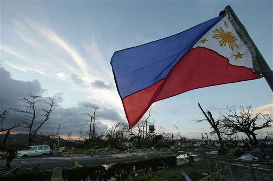 A Philippine flag stands amongst the damage caused after powerful Typhoon Haiyan slammed into Tacloban city, Leyte province, central Philippines on Saturday, Nov. 9, 2013. Rescuers in the central Philippines counted at least 100 people dead and many more injured Saturday, a day after one of the most powerful typhoons on record ripped through the region, wiping away buildings and leveling seaside homes with massive storm surges. (AP Photo/Aaron Favila) Photo: Aaron Favila / AP2013