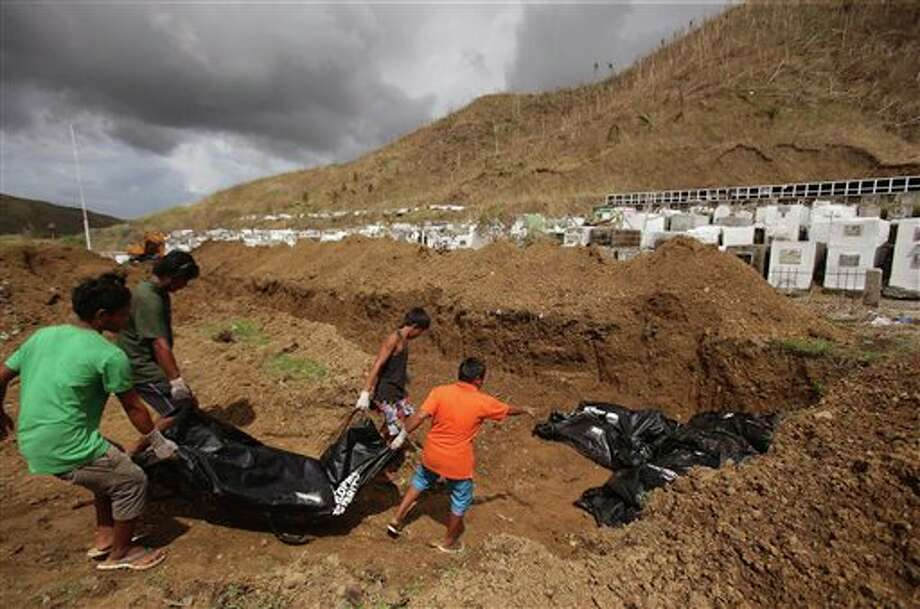 Workers start to arrange body bags at a mass burial site at the Basper public cemetery in Tacloban, Leyte province, central Philippines on Thursday, Nov. 14, 2013. Workers in the typhoon-shattered city buried 100 of its thousands of dead in a hillside mass burial Thursday as desperately needed aid began to reach some of the half-million people displaced by the disaster. (AP Photo/Aaron Favila) Photo: Aaron Favila / AP