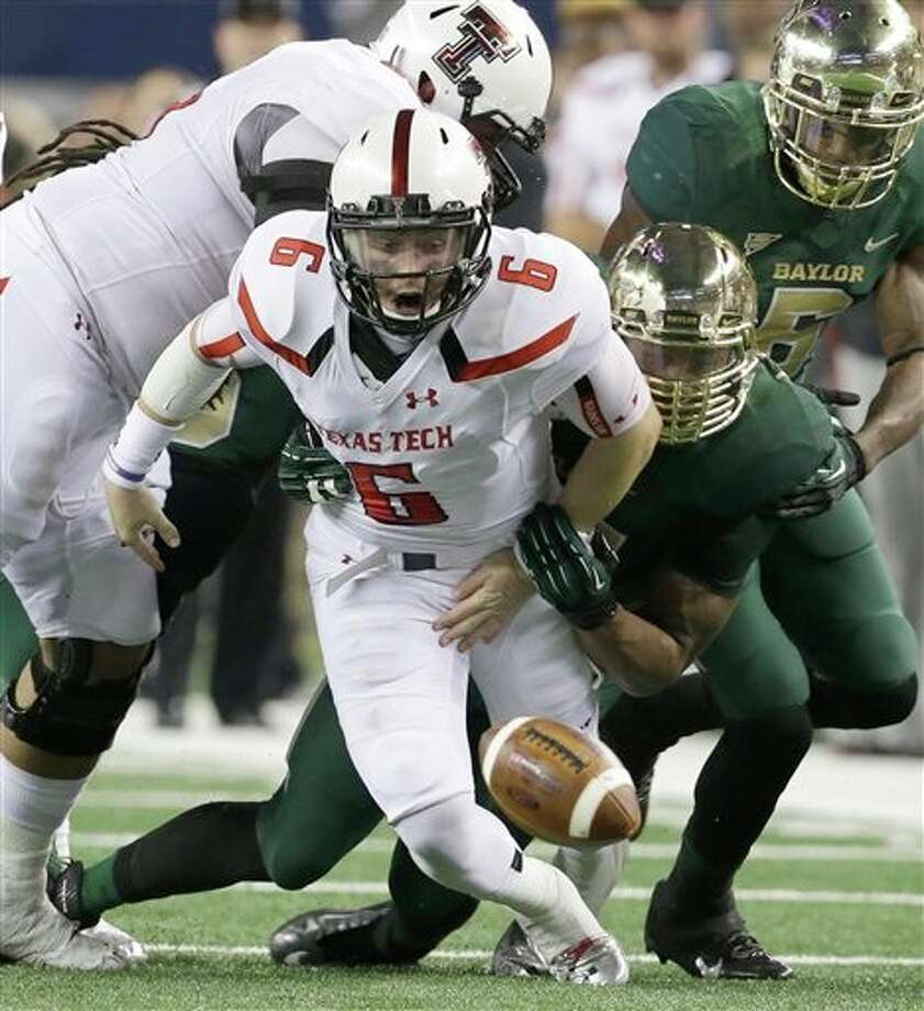 Texas Tech quarterback Baker Mayfield (6) fumbles as Baylor comes in to recover the loose ball during the first half of an NCAA college football game in Arlington, Texas, Saturday, Nov. 16, 2013. (AP Photo/LM Otero) Photo: LM Otero / AP