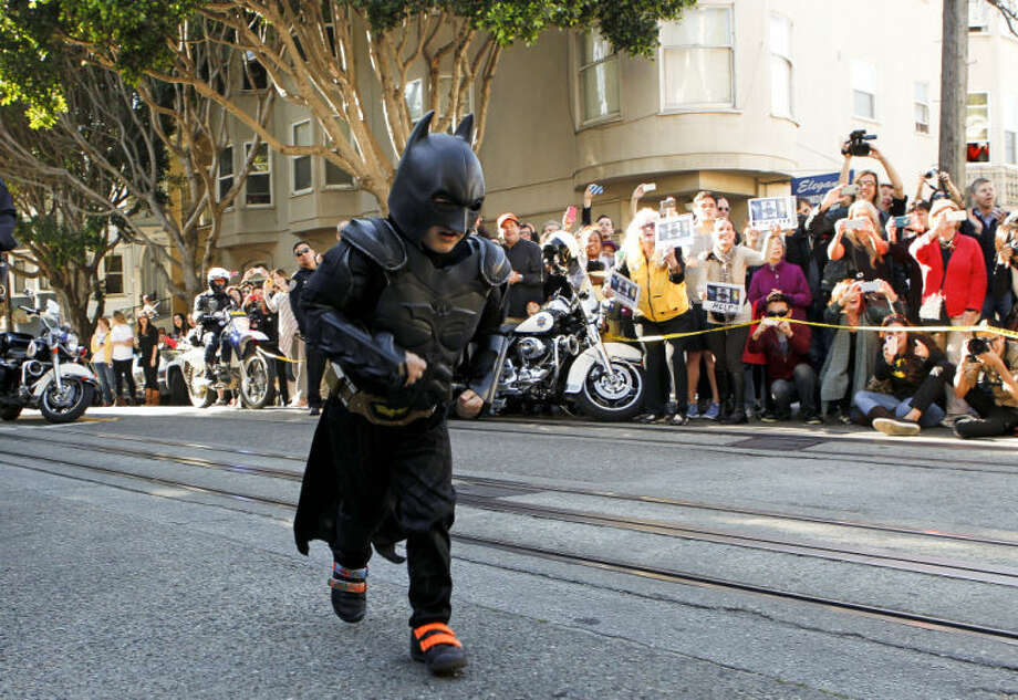 Miles as Batkid runs to the scene of a report of a damsel in distress along the Hyde Street cable car line in San Francisco Ca., on Friday Nov. 15, 2013. Five year old Miles from Tulelake in Siskiyou County loves superheroes and Batman in particular. After battling leukemia since he was a year old Miles will fulfill his dream of becoming Batkid being swept around the city performing superhero feats from rescuing a damsel in distress to thwarting a bank robbery and even chasing down the Penguin through AT&T Park Photo: Michael Macor