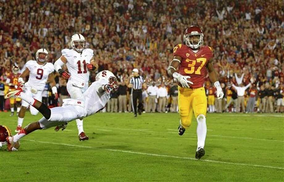 Southern California running back Javorius Allen, right, runs in for a touchdown as Stanford safety Jordan Richards, front left, linebacker James Vaughters, left, and linebacker Shayne Skov give chase during the first half of an NCAA college football game, Saturday, Nov. 16, 2013, in Los Angeles. (AP Photo/Mark J. Terrill) Photo: Mark J. Terrill / AP