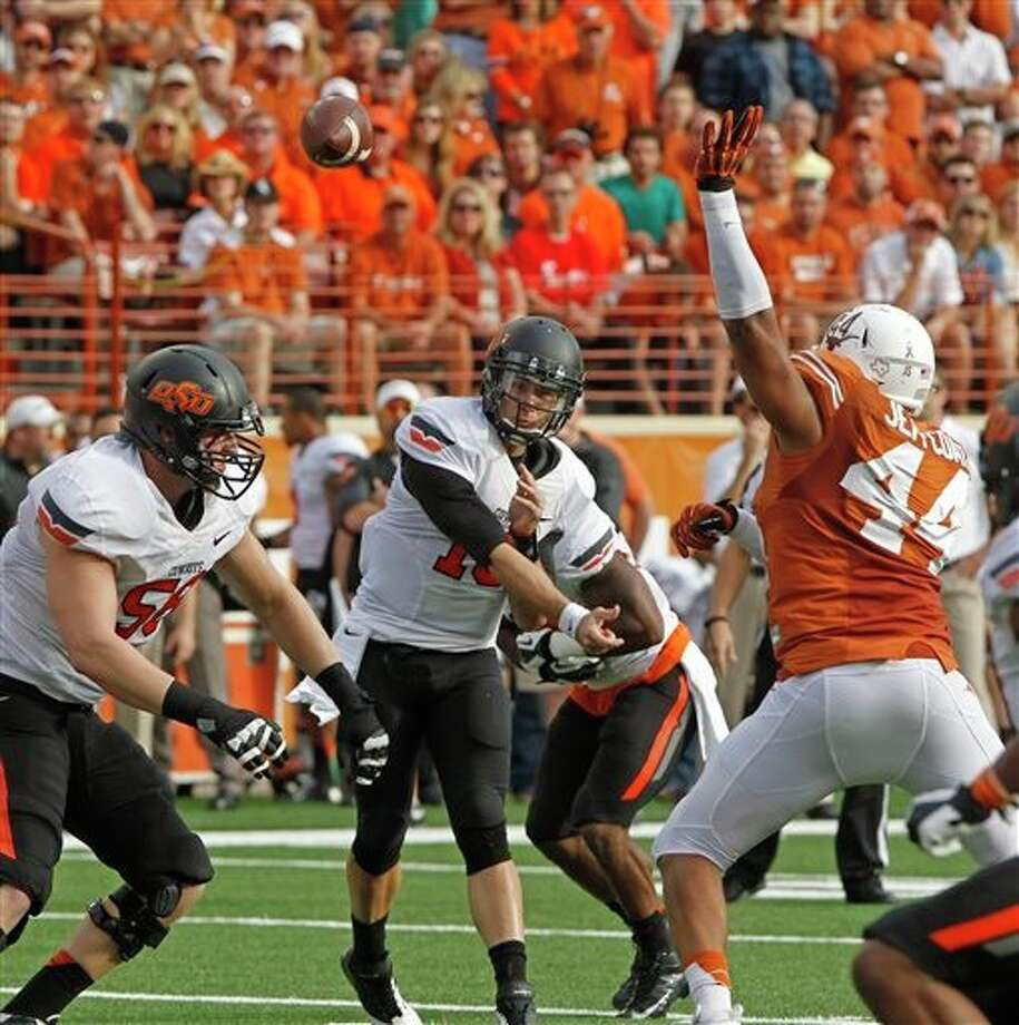 Oklahoma State quarterback Clint Chelf (10) passes against Texas defensive end Jackson Jeffcoat (44) during the first quarter of an NCAA college football game Saturday, Nov. 16, 2013, in Austin, Texas. Oklahoma State won 38-13. (AP Photo/Michael Thomas) Photo: Michael Thomas / FR65778 AP