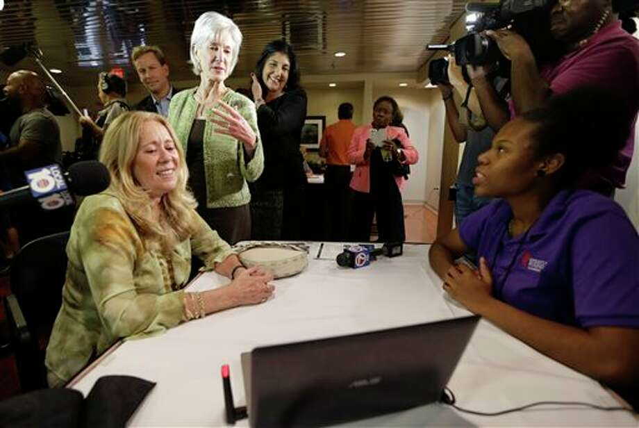 Department of Health and Human Services Secretary Kathleen Sebelius, center, talks with navigator Frantcia Thenor, right, and Carmen Celeiro, left, about health care options available under the Affordable Care Act, at the North Shore Medical Center, Tuesday, Nov. 19, 2013, in Miami. Sebelius visited Miami and Orlando Tuesday to talk up the Affordable Care Act as fallout from the new law grows. (AP Photo/Lynne Sladky) Photo: Lynne Sladky / AP