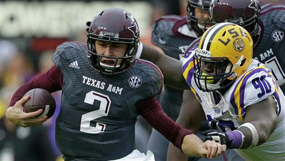 Texas A&M quarterback Johnny Manziel (2) tries to elude LSU defensive tackle Anthony Johnson (90) in the first half of an NCAA college football game in Baton Rouge, La., Saturday, Nov. 23, 2013. (AP Photo/Gerald Herbert) Photo: Gerald Herbert / AP