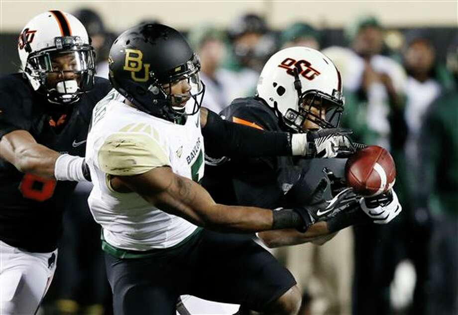 Oklahoma State linebacker Joe Mitchell (29) breaks up a pass intended for Baylor wide receiver Antwan Goodley (5) in the fourth quarter of an NCAA college football game in Stillwater, Okla., Saturday, Nov. 23, 2013. Oklahoma State won 49-17. (AP Photo/Sue Ogrocki) Photo: Sue Ogrocki / AP