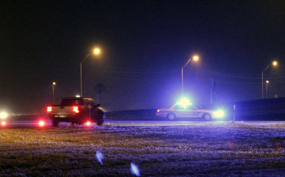 Midland Police stationed a vehicle and red flares on the westbound lanes of 191 to warn motorists to slow down and watch for black ice on bridges Saturday. James Durbin/Reporter-Telegram Photo: JAMES DURBIN