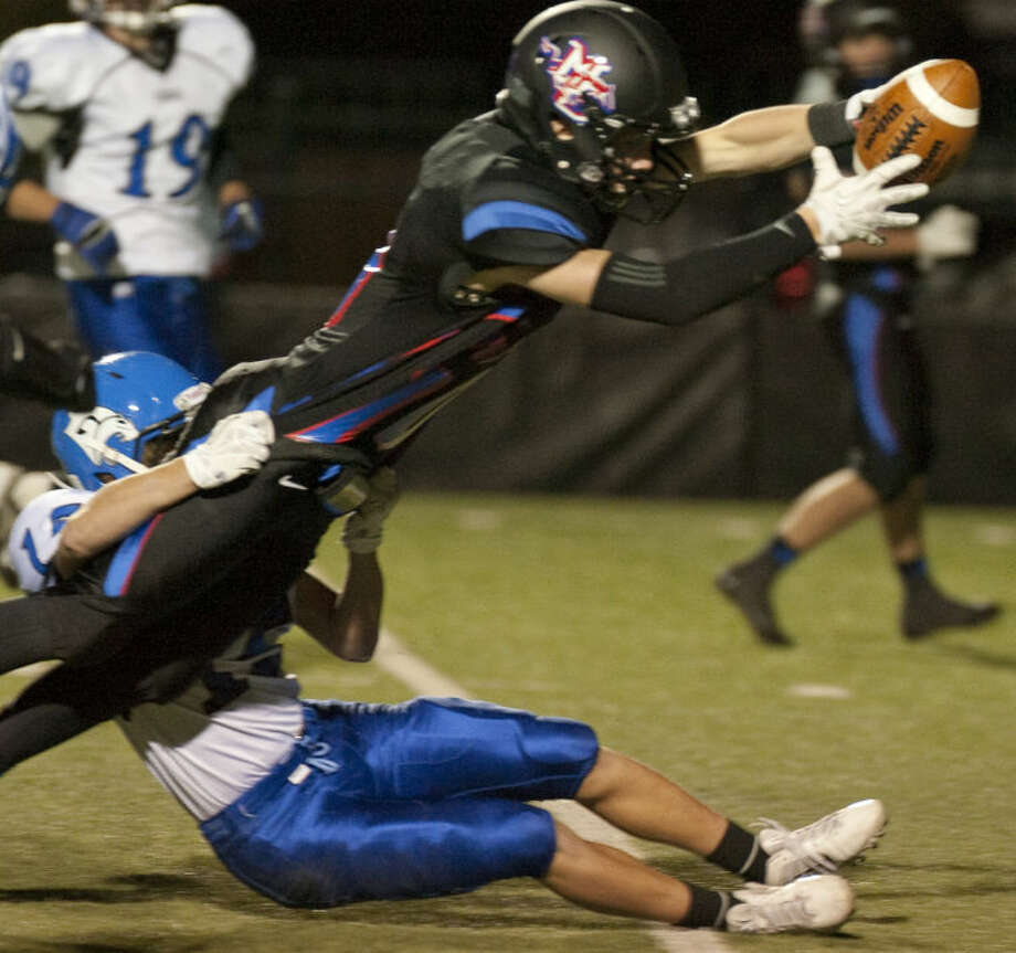Midland Christian's Grant Little tries to dive foward for extra yards as Tyler Grace's Jackson Nickel holds on Friday evening at Mustang Field. Tim Fischer\Reporter-Telegram Photo: Tim Fischer