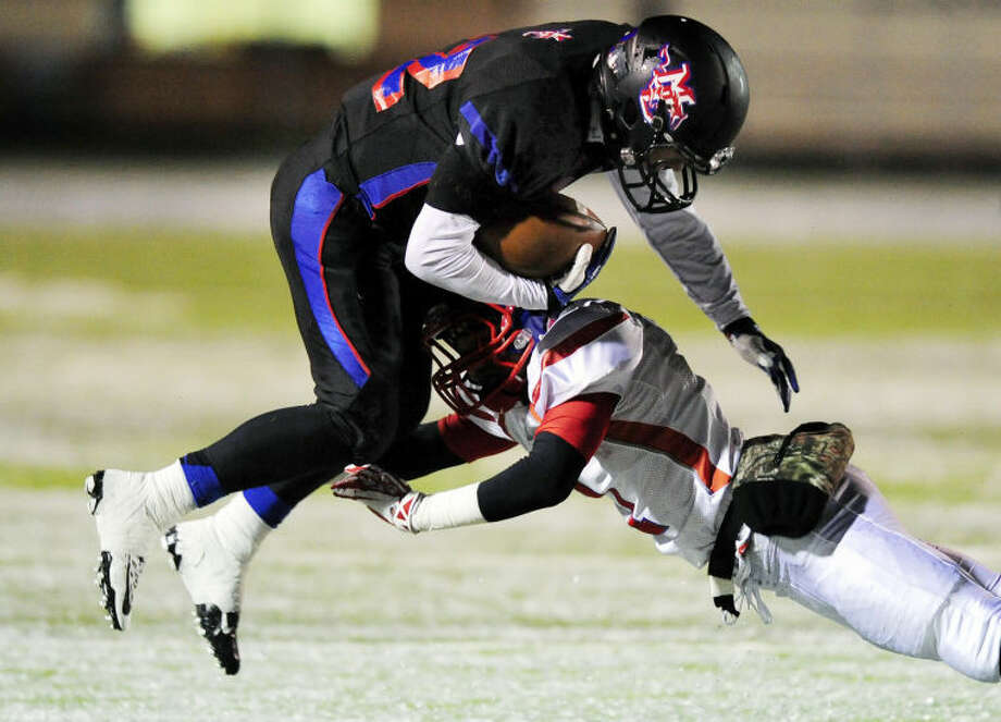 Midland Christian fullback Justin Fender (left) gets tackled by Dallas Parish Episcopal's defensive back Zavier Suggs during a TAPPS Division II Regional playoff game at Bulldog Stadium in Clyde on Saturday. Photo: Eric J. Shelton