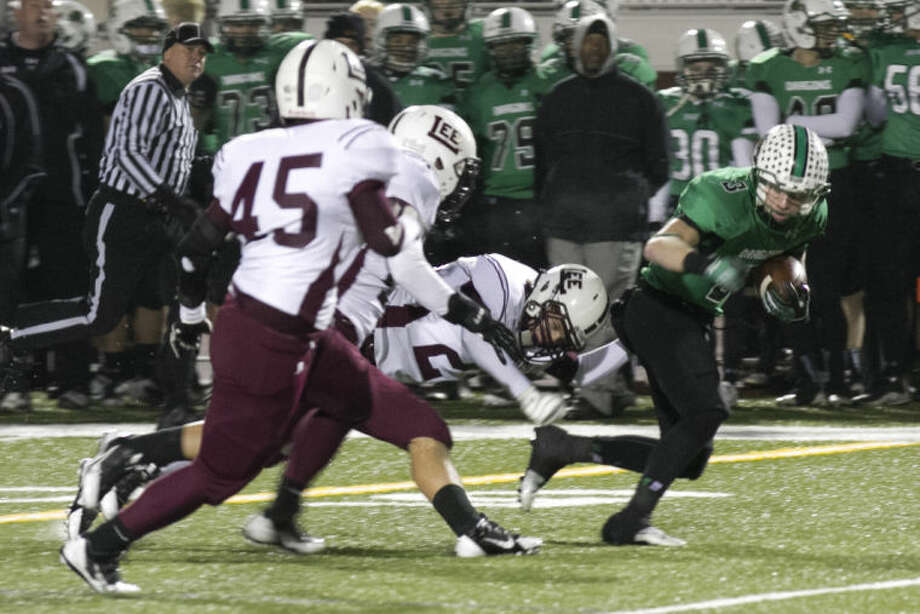Gavin Arison (3) of Southlake Carroll, is brought down by Jon Schwalbach (Midland Lee) during their playoff game at Chisholm Trail Stadium in Fort Worth on Nov,. 22, 2013. Photo by: Scott Pearson Photo: Scott Pearson