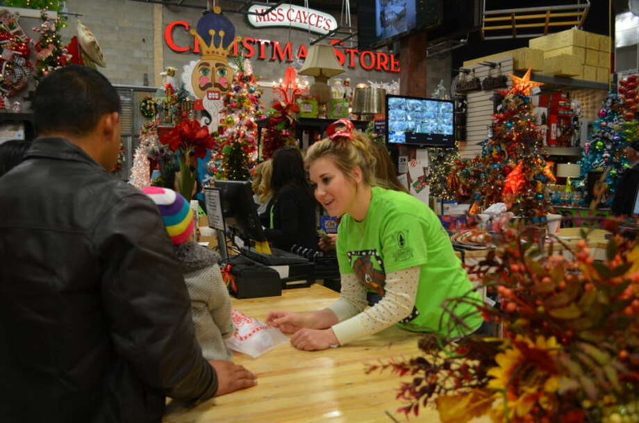 Brylie Hanlan, a 21-year-old seasonal worker at Miss Cayce's Christmas Store, helps a customer Saturday. The boom is creating wealth and job opportunities, but seasonal employment is hard to find, especially at Miss Cayce's, which could use at least 10 more workers, said co-owner Becky McCraney. Photo: James Cannon / MRT
