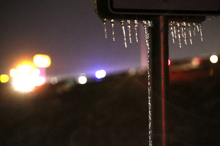 Icecicles hang from a sign as Midland public safety personnel work a vehicle accident in the background near the 191 and FM 1788 overpass Saturday. James Durbin/Reporter-Telegram Photo: JAMES DURBIN