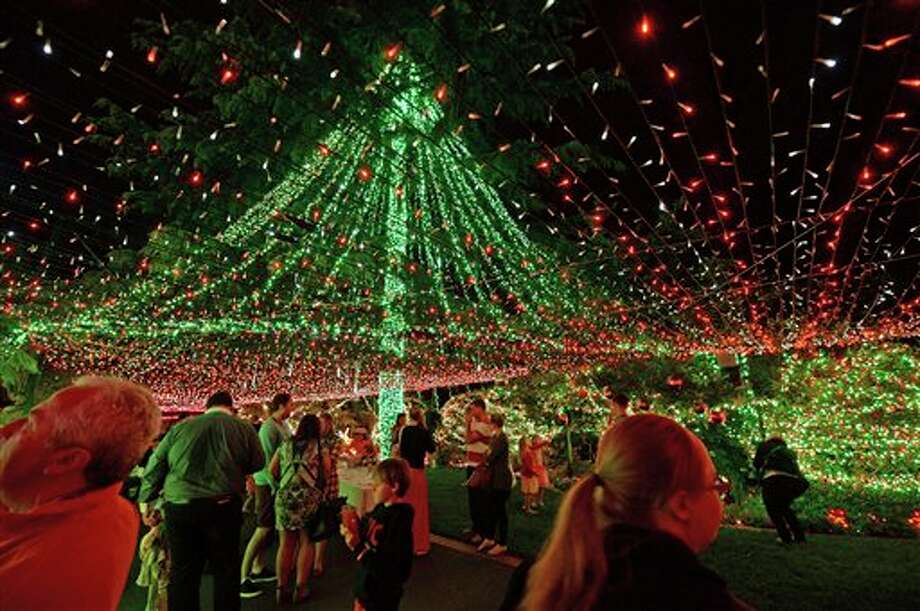 People look at The Richards home illuminated with miniature lights in Canberra, Sunday, Nov. 24, 2013. The Australian family has reclaimed their Guinness World Record by stringing up more than half a million Christmas lights around their suburban home. Guinness World Records official Chris Sheedy confirmed Monday, Nov. 25, that the Richards family set the record for Christmas lights on a residential property with 502,165 twinkling bulbs. (AP Photo/AAPIMAGE, Alan Porritt) NO ARCHIVING, AUSTRALIA OUT, NEW ZEALAND OUT, PAPUA NEW GUINEA OUT, SOUTH PACIFIC OUT, NO SALES Photo: Alan Porritt / AAP