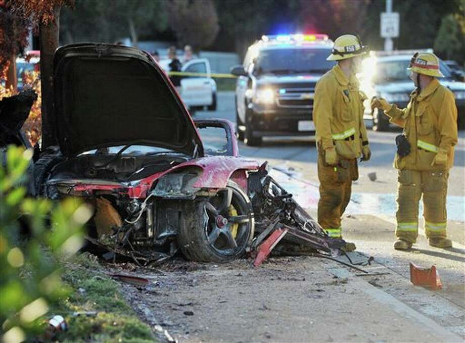 "Sheriff's deputies work near the wreckage of a Porsche that crashed into a light pole on Hercules Street near Kelly Johnson Parkway in Valencia, Calif., on Saturday, Nov. 30, 2013. A publicist for actor Paul Walker says the star of the ""Fast & Furious"" movie series died in the crash north of Los Angeles. He was 40. Ame Van Iden says Walker died Saturday afternoon. No further details were released. (AP Photo/The Santa Clarita Valley Signal, Dan Watson) Photo: Dan Watson / The Santa Clarita Valley Signal"