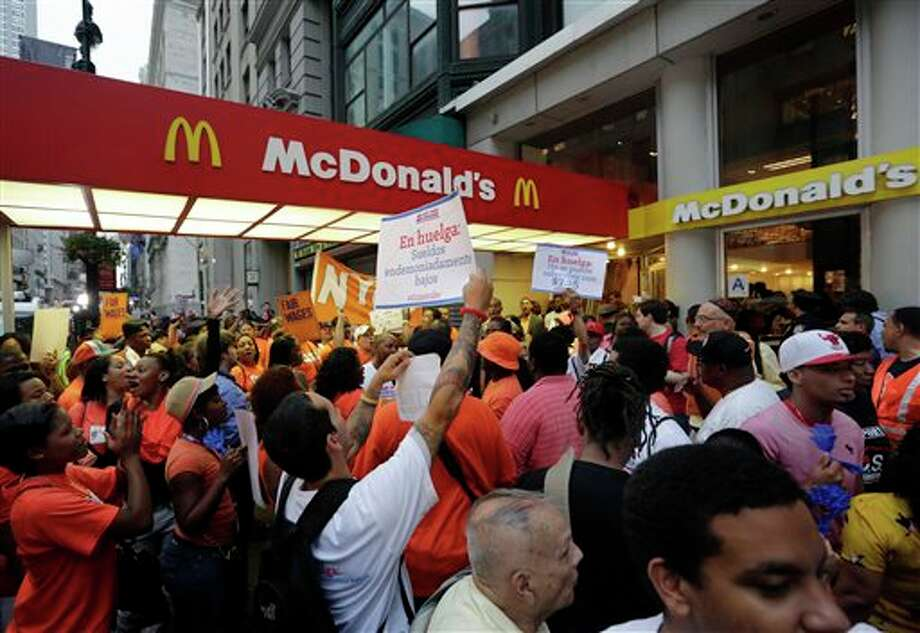 FILE - In this Thursday, Aug. 29, 2013, file photo, protesting fast food workers demonstrate outside a McDonald's restaurant on New York's Fifth Avenue, in New York. Fast-food workers in about 100 cities will walk off the job Thursday, Dec. 5, 2013, to build on a campaign that began about a year ago to call attention to the difficulties of living on the federal minimum wage of $7.25 an hour. (AP Photo/Richard Drew, File) Photo: Richard Drew / AP