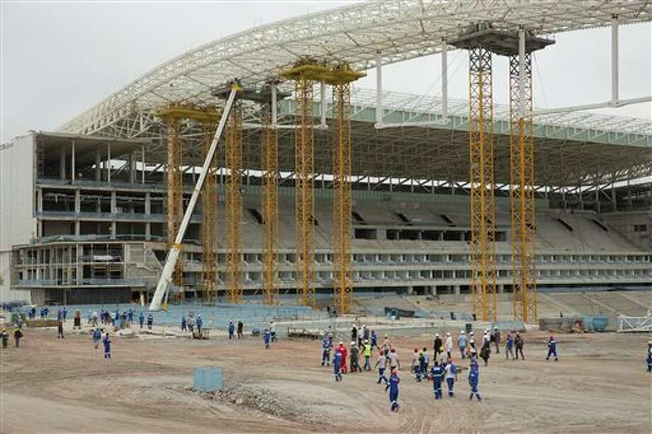 Construction workers return to the Arena Corinthians stadium that will host the opening match of the World Cup, five days after an accident killed two workers, in Sao Paulo, Brazil, Monday, Dec. 2, 2013. Construction company Odebrecht had suspended work on the site after a crane collapsed on Wednesday, Nov. 27, as it was hoisting a 500-ton piece of roofing. (AP Photo/Andre Penner) Photo: Andre Penner / AP
