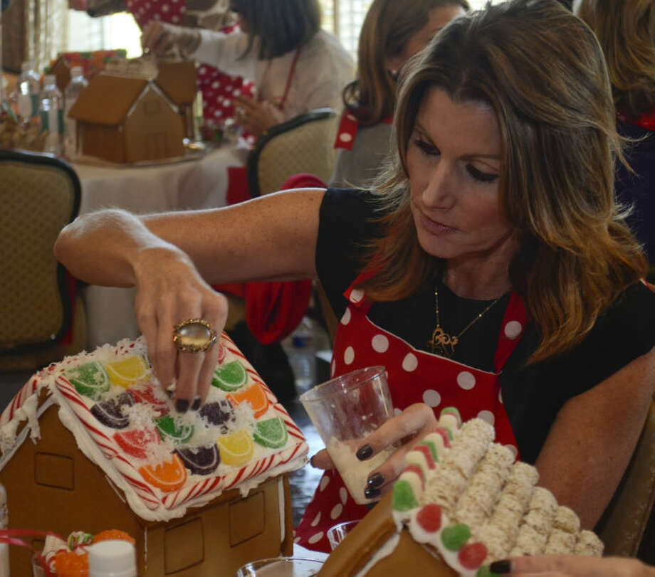 Harriet Essman works on her gingerbread house as she and others help raise money for Fair Havens at the second Gingerbread Haven luncheon. Tim Fischer\Reporter-Telegram Photo: Tim Fischer