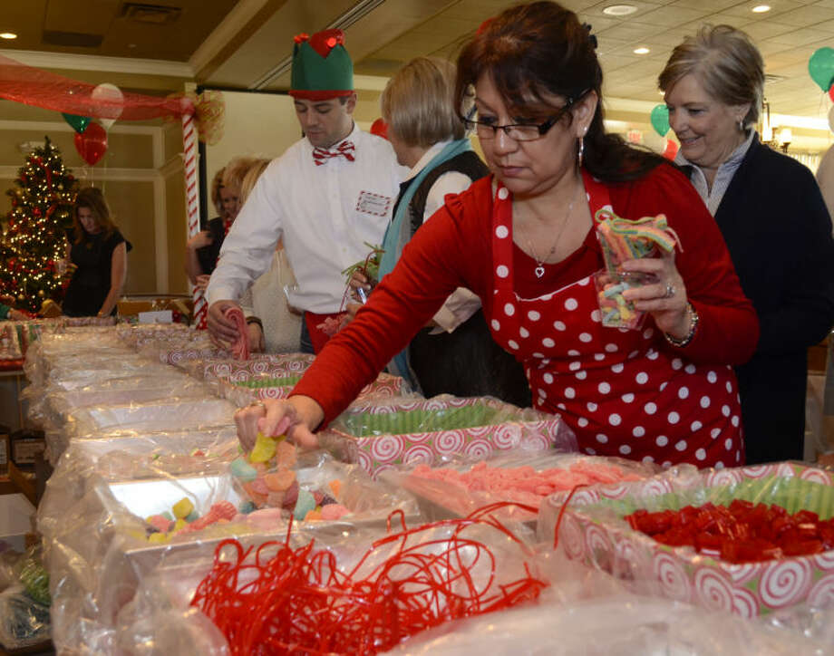 Margie Bickford gathers candy to decorate her gingerbread house as she and others help raise money for Fair Havens at the second Gingerbread Haven luncheon. Tim Fischer\Reporter-Telegram Photo: Tim Fischer