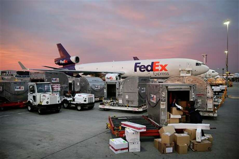 Brenda Thompson, right, loads packages into a container at the FedEx hub at Los Angeles International Airport on Monday, Dec. 2, 2013, in Los Angeles. Millions of Americans took advantage of online deals ranging from free shipping to hundreds of dollars off electronics and half-price clothing Monday, which was expected to be the busiest online shopping day of the year. (AP Photo/Jae C. Hong) Photo: Jae C. Hong / AP