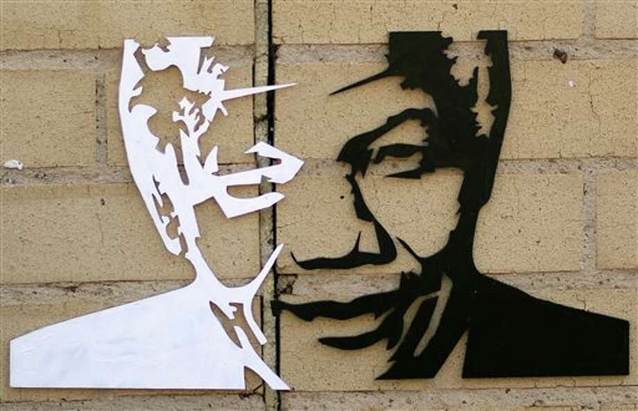 FILE - In this July 16, 2013 file photo, a portrait of former South African President Nelson Mandela is attached to a wall outside the Mediclinic Heart Hospital where he was being treated in Pretoria, South Africa. On Thursday, Dec. 5, 2013, Mandela died at the age of 95. (AP Photo/Themba Hadebe) Photo: Themba Hadebe / AP