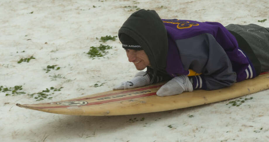 Joseph Perez holds on to a surf coard as he sleds down a hill at Cowden Park Friday morning. Tim Fischer\Reporter-Telegram Photo: Tim Fischer