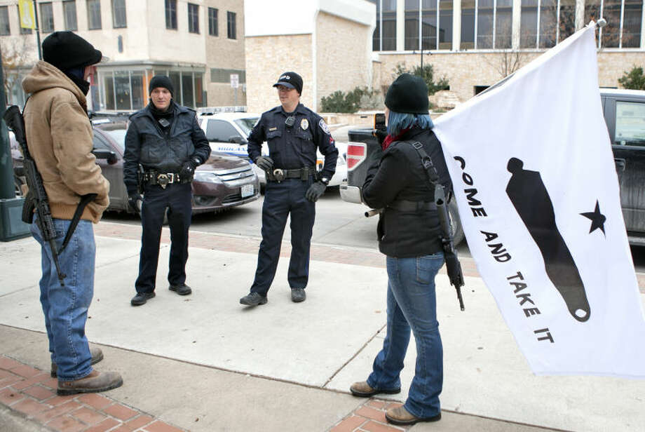 "Stephanie McDonald and James Franklin make small talk with Midland Police officers while participating in an open carry demonstration Saturday in Centennial Plaza. ""We want to educate the public concerning our legal rights and help people become accustomed to the idea of responsible people carrying firearms,"" said Franklin. James Durbin/Reporter-Telegram Photo: JAMES DURBIN"