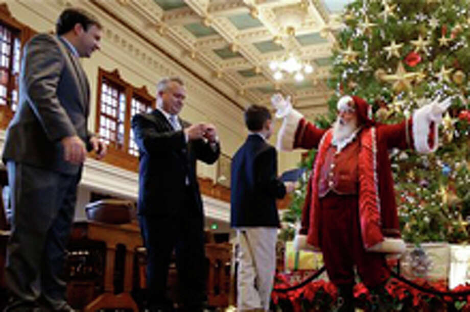 Bill French, right, dressed as Santa Claus, talks with Reagan Bohac, 8, right, son of State Representative Dwayne Bohac, R-Houston, second from left, on the house floor following a news conference at the state capitol, Monday, Dec. 9, 2013, in Austin , Texas. Rep. Bohac was trying to raise awareness for the Texas' new Merry Christmas law that allows teachers, students, parents and school administrators to celebrate traditional winter holidays like Christmas and Hanukah in public schools without fear of censorship, persecution, or litigation. (AP Photo/Eric Gay) Photo: Eric Gay