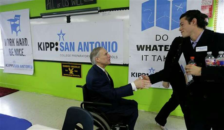 Republican Attorney General Greg Abbott, left, visits with educators at KIPP: San Antonio, Wednesday, Dec. 11, 2013, in San Antonio. Abbott and Democratic state Sen. Wendy Davis are already trading barbs over public schools, despite neither yet unveiling an education platform - signaling a potentially more intense education debate ahead than in past gubernatorial elections. (AP Photo/Eric Gay) Photo: Eric Gay / AP