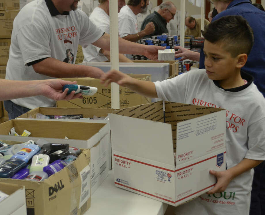 Israel Ramirez Jr. helps pack special boxes to be sent to his father's buddies currently serving with Israel Ramirez Sr. in Afghanistan with their Army Reserve unit. Tim Fischer\Reporter-Telegram Photo: Tim Fischer