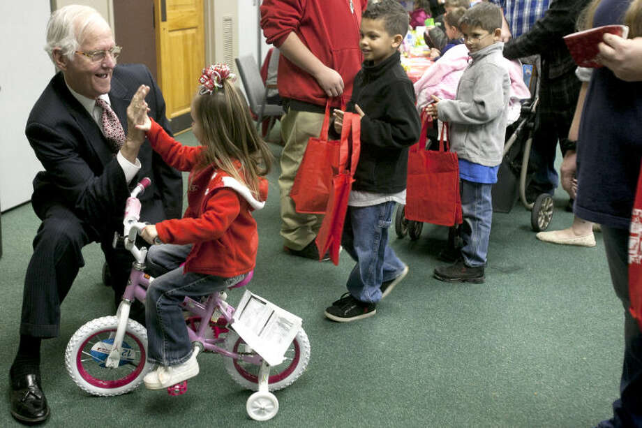 "Midland County Judge Mike Bradford high-fives Mackenzie Taylor, age 3, while she rides her new bike during the Centers for Children & Families ""Operation Elf"" event Wednesday at the Junior League of Midland. James Durbin/Reporter-Telegram Photo: JAMES DURBIN"