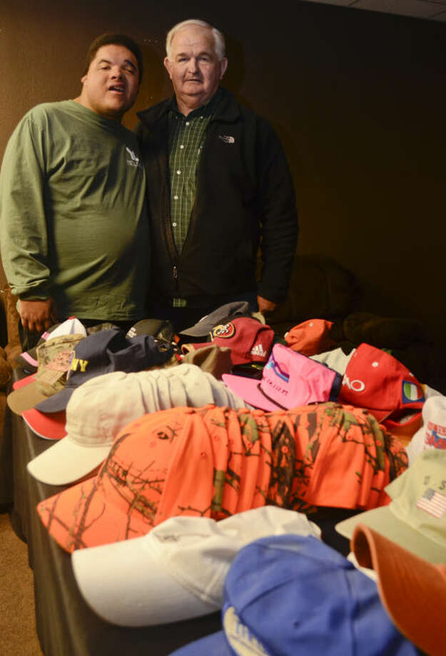 Larry Cox and his son Justin show some of the hats they collected to donate to MARC. Tim Fischer\Reporter-Telegram Photo: Tim Fischer